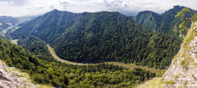 Panoramic photo of spectacular river canyon in Pieniny, Poland. Winding Dunajec surrounded by mountain slopes covered with forest.